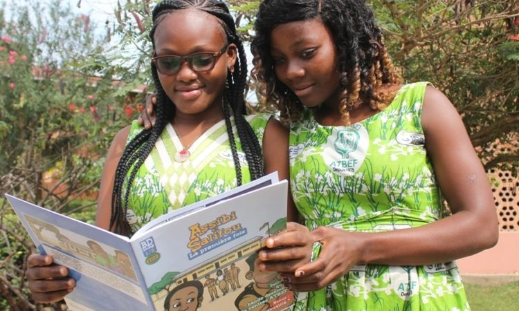 "Togolese teenagers share a copy of the USAID-funded comic book ""Assibi et Salifou, la première fois"" which aims to promote better sexual health among youth and adolescents"